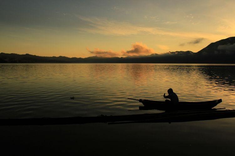 Seorang nelayan sedang mencari ikan saat matahari menyingsing di Danau Batur, yang merupakan danau di kaldera Gunung Batur pada ketinggian 1.050 mdpl. Permukaan air Danau Batur seluas 16.05 KM2, yang terletak di Kintamani, Kabupaten Bangli, Bali.