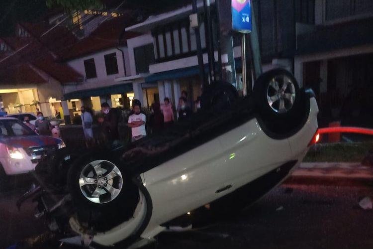 Sebuah mobil Honda CRV warna putih terbalik dan menjadi tontonan warga, di Jalan Kartika Plaza, Kuta, Badung, Bali, Minggu (25/4/2021) malam.