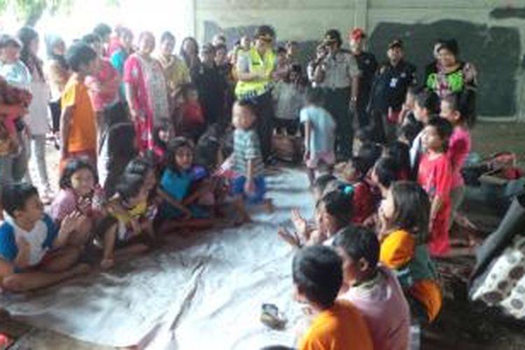 Polwan dari Polres Metro Jakarta Selatan menghibur dengan mengajak anak anak korban pengungsian banjir di Tebet, Jakarta Selatan bermain dan mengikuti lomba. Senin (20/1/2014).