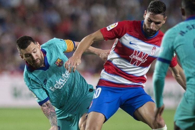Lionel Messi mencoba merebut bola dari Antonio Puertas pada pertandingan Granada vs Barcelona dalam lanjutan Liga Spanyol di Los Carmenes, 21 September 2019.