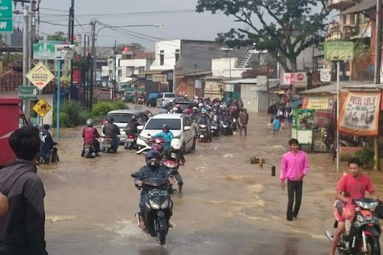 Tampak salah satu jalan di Kabupaten Bandung terendam Banjir, kendaraan tersendat.