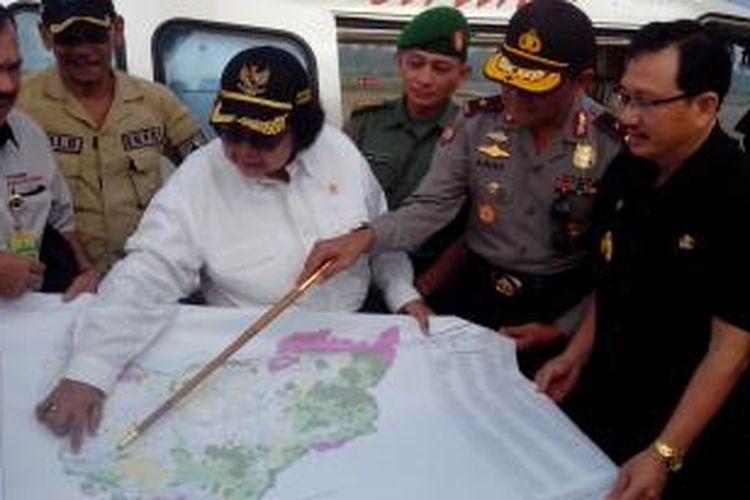 Menteri Lingkungan Hidup dan Kehutanan, Siti Nurbaya Bakar, beserta rombongan memperlihatkan peta sebelum take off menggunakan heli memantau titik api di Kalimantan Barat (10/7/2015)