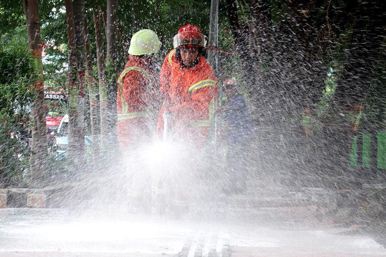 Petugas pemadam kebakaran menyemprotkan cairan disinfektan ke trotoar di Makassar, Sulawesi Selatan, Minggu (22/3/2020). Penyemprotan cairan disinfektan tersebut  guna mengurangi resiko penularan virus corona atau COVID-19 di sejumlah are publik mengingat telah ditemukannya dua kasus positif di Sulsel dan salah satu diantaranya meninggal dunia.