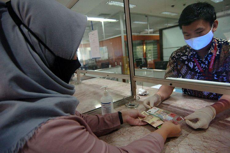 Petugas melayani warga transaksi penukaran uang baru pecahan Rp 75.000 saat penukaran Uang Peringatan Kemerdekaan 75 Tahun Republik Indonesia di Kantor Perwakilan (Kpw) Bank Indonesia (BI), Tegal, Jawa Tengah, Selasa (18/8/2020). Kpw BI Kota Tegal menyediakan sebanyak 1,3 juta lembar uang baru pecahan Rp 75.000 untuk ditukarkan warga dengan syarat daftar online dan menunjukkan KTP elektronik.