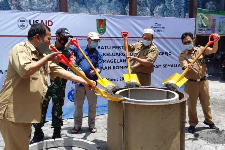 Mukh Ma'ruf (kedua dari kanan) Kepala Desa Pucungrejo, Kecamatan Muntilan, Kabupaten Magelang menuangkan material cor pada cetakan jamban pada peluncuran Pembangunan Jamban Layak Keluarga di Desa Pucungrejo, Selasa (23/3/2021), di Balai Desa Pucungrejo. Program ini hasil kerjsa sama Kelompok Swadaya Masyarakat Semali Asri Desa Pucungrejo, USAID-IUWASH PLUS, dan didanai oleh Yayasan Dana Kemanusiaan Kompas.