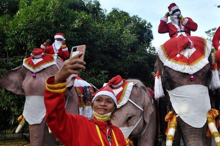 Gajah dari Istana Gajah Ayutthaya, mengenakan kostum Sinterklas dan menggunakan masker wajah, berpose untuk foto menjelang acara membagikan masker wajah kepada siswa di luar Sekolah Jirasat Wittaya di provinsi Ayutthaya Thailand pada Rabu (23/12/2020).