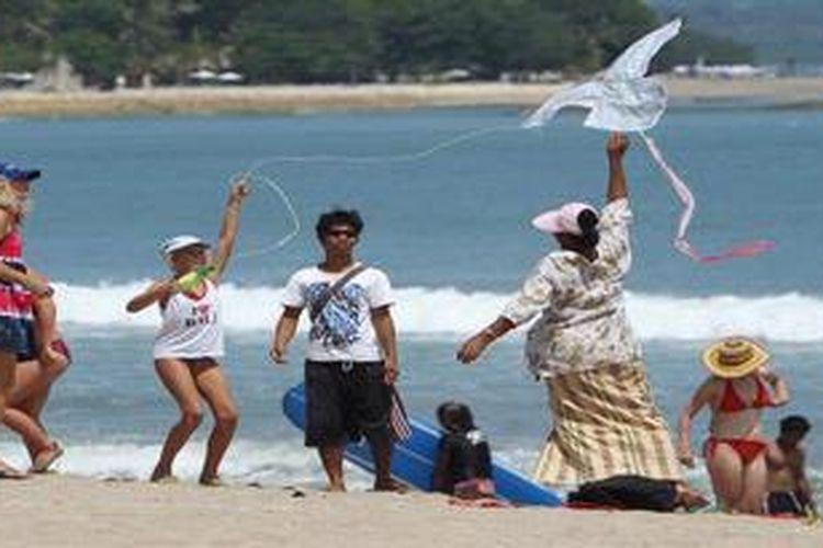 Wisatawan bermain layang-layang di Pantai Kuta, Bali, Senin (25/4/2011).