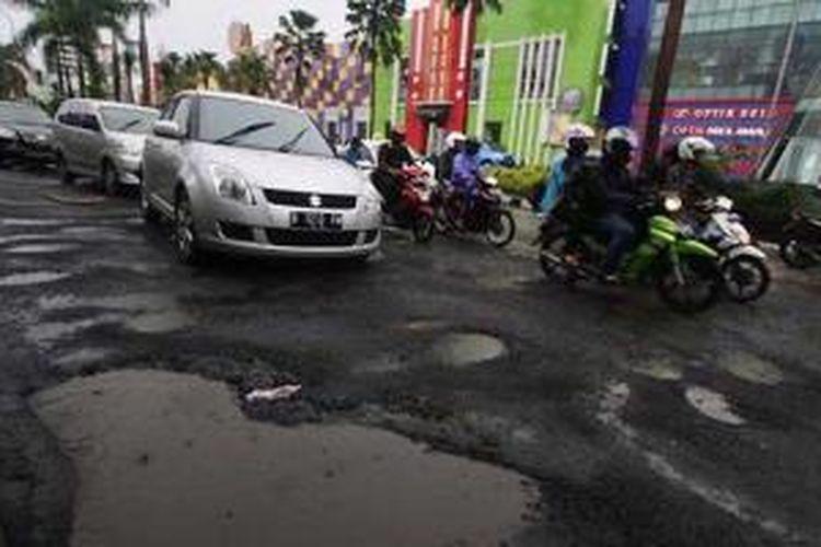 Jalan rusak akibat banjir, akan diganti dengan lapisan beton.