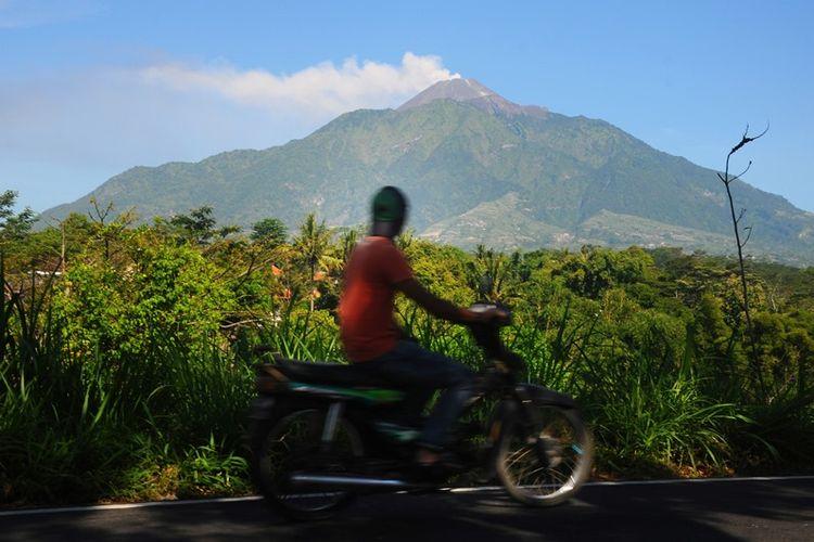 Pengendara melintas di jalur Boyolali-Magelang berlatar belakang letusan freatik Gunung Merapi di Cepogo, Boyolali, Jawa Tengah, Jumat (11/5). Berdasarkan data Badan Nasional Penanggulangan Bencana (BNPB) terjadi letusan freatik Gunung Merapi disertai suara gemuruh dengan tekanan sedang hingga kuat dan tinggi kolom 5.500 meter dari puncak kawah pada pukul 07.32 WIB.