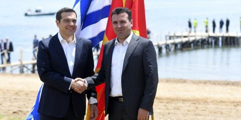 Perdana Menteri Macedonia Zoran Zaev (kanan) menyambut Perdana Menteri Yunani Alexis Tsipras (kiri) di tepi Danau Prespa dekat Otesevo Minggu (17/6/2018) dalam kesepakatan pergantian nama Macedonia menjadi Republik Macedonia Utara. (AFP/Maja Zlatevska)