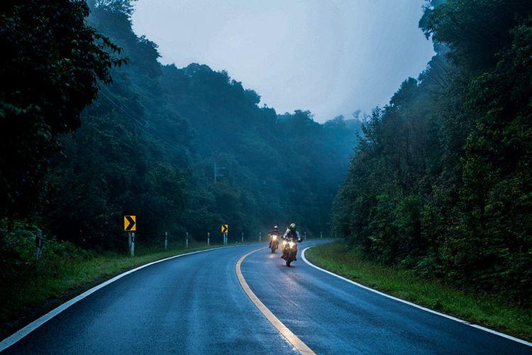 Travelling naik sepeda motor.