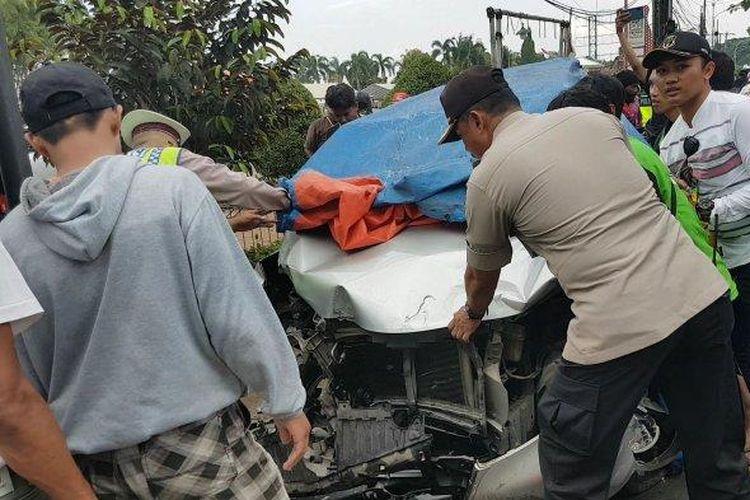 Polisi dengan warga sekitar mengevakuasi satu unit mobil Toyota Avanza yang terlibat kecelakaan maut.