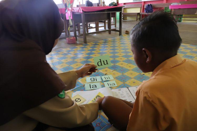 Warsiah, Kepala SDN 013 Desa Bulu Perindu, Kecamatan Tanjung Selor, Kalimantan Utara memberikan bimbingan membaca kepada siswa dengan metode kartu baca.