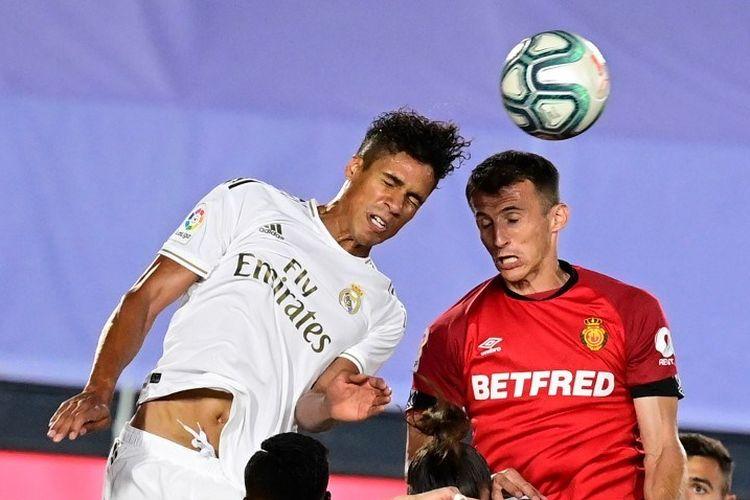 Raphael Varane (kiri) berduel dengan Ante Budimir (kanan) pada laga Real Madrid vs Mallorca di Stadion Alfredo Di Stefano dalam lanjutan pekan ke-31 LaLiga, kasta teratas Liga Spanyol, Rabu 24 Juni 2020.
