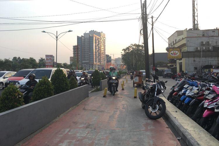 Jalur pedestrian dilintasi pengendara sepeda motor di pedestrian Jalan KH. Noer Ali, Kalimalang mengarah ke lampu merah atau perempatan Bekasi Cyber Park (BCP), Senin (17/7/2017) sore.