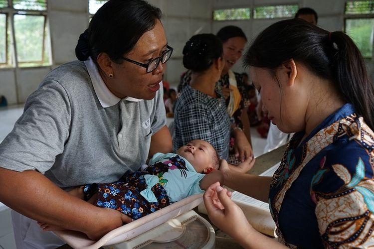 Relawan mendampingi seorang ibu yang sedang mengikuti kegiatan di posyandu, Desa Mantan, Kabupaten Kapuas Hulu, Kalimantan Barat.