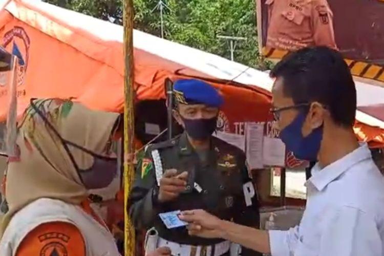 Ketua KPU Sumbar Amnasmen memperlihatkan KTP nya kepada petugas PSBB kota Padang, Rabu (13/5/2020)