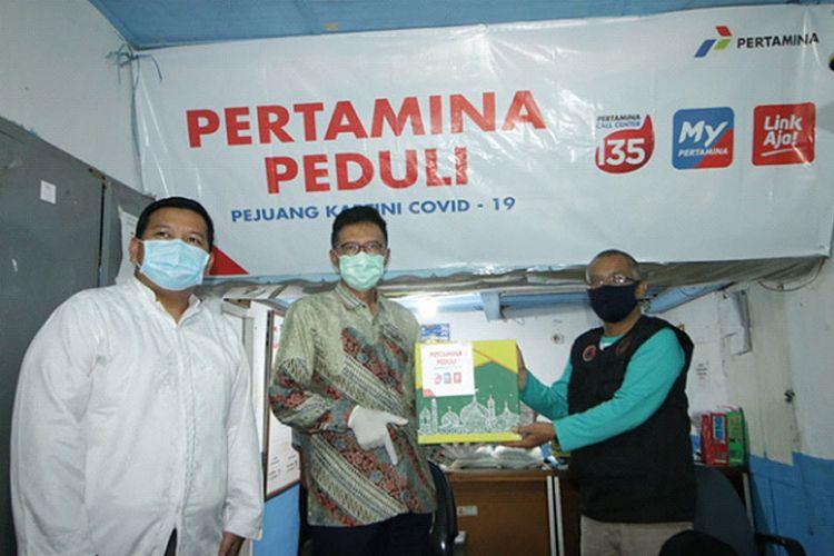 Penyerahan bantuan secara simbolis paket sembako kepada masyarakat di Makassar.