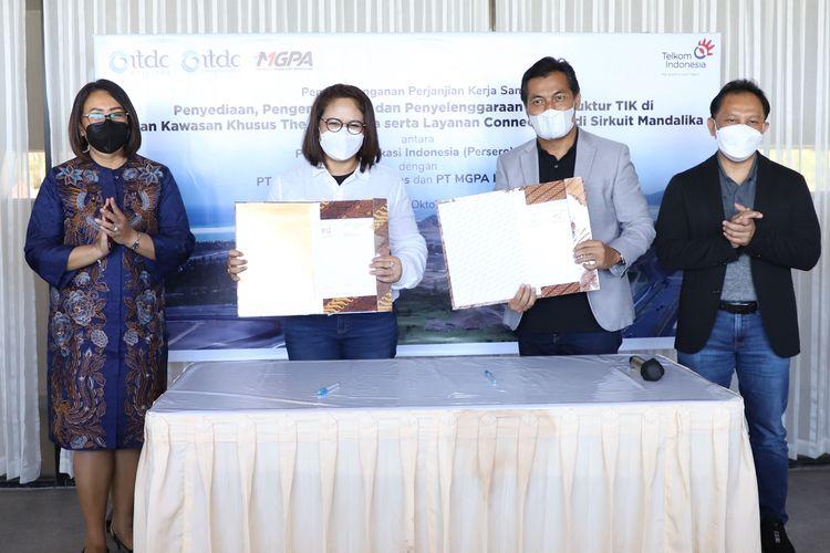 Direktur Enterprise and Business Service PT Telkom Indonesia (Persero) Tbk (Telkom) Edi Witjara (paling kanan) dan Direktur Pengembangan Bisnis PT Pengembangan Pariwisata Indonesia (Persero) atau Indonesia Tourism Development Corporation (ITDC) Ema Widiastuti (paling kiri) menyaksikan penandatanganan Perjanjian Kerja Sama (PKS) tentang Penyelenggaraan Infrastruktur dan Pemasaran Layanan Teknologi Informasi dan Komunikasi (TIK) di Jalan Kawasan Khusus (JKK) The Mandalika yang dilakukan oleh Executive Vice President Divisi Enterprise Service Telkom Mohammad Salsabil (kedua dari kanan) dan Direktur Utama PT ITDC Nusantara Utilitas (ITDC NU), anak usaha ITDC, A.A. Istri Ratna Dewi (kedua dari kiri) di The Mandalika, Lombok (7/10).