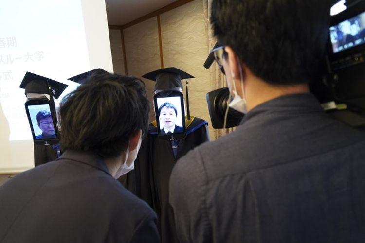 Perwakilan wisudawan dalam wisuda online dan menggunakan robot avatar di Hotel Grand Palace, Tokyo, Jepang, Sabtu (28/3/2020). Penggunaan robot ini dioperasikan dari jarak jauh oleh perwakilan wisudawan dan wisudawan lain bisa menyaksikan prosesi wisuda online melalui Zoom.