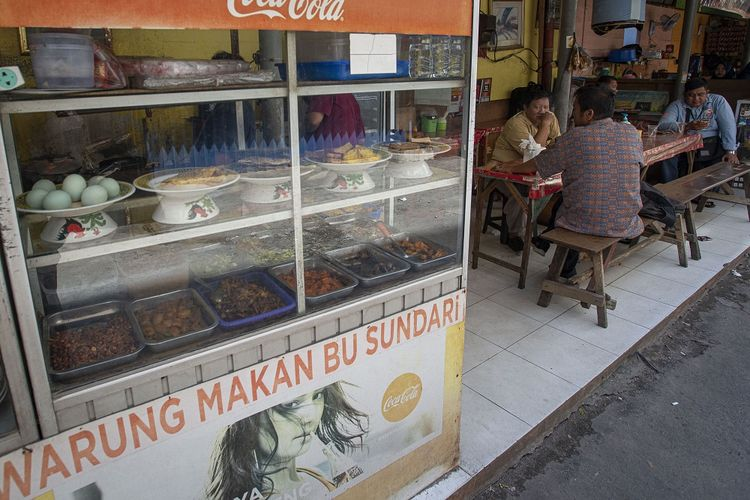 Sejumlah warga menyantap sajian yang dijual salah satu warung makan di Kemayoran, Jakarta, Senin (26/7/2021). Pemerintah menyesuaikan aturan Pemberlakuan Pembatasan Kegiatan Masyarakat (PPKM) level 4 pada pelaku usaha kuliner dengan mengizinkan warung makan, pedagang kaki lima, lapak jajanan dan sejenisnya untuk buka dengan protokol kesehatan yang ketat sampai dengan pukul 20.00, menerima maksimal pengunjung makan di tempat tiga orang dan waktu makan maksimal 20 menit. ANTARA FOTO/Aditya Pradana Putra/foc.