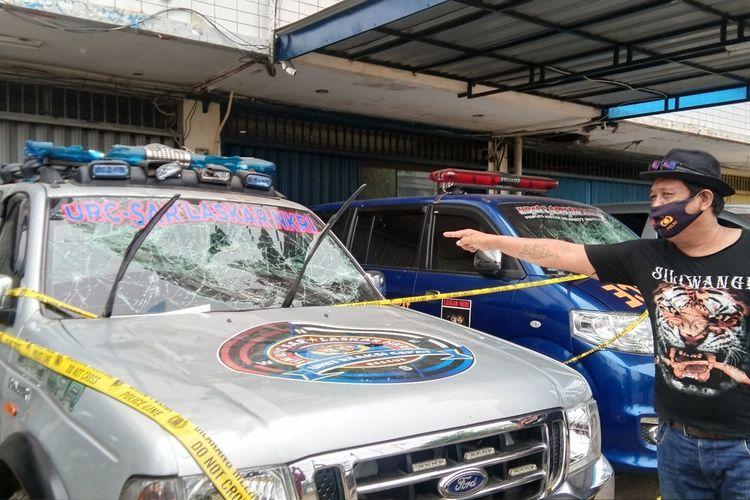Seseorang menunjukkan mobil yang bagian depannya rusak akibat penyerangan di Kantor LSM NKRI, Karawang, Jawa Barat.