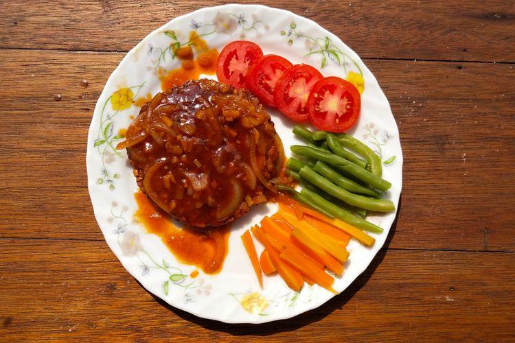 Ilustrasi steak tempe dengan saus dan sayur pelengkap.