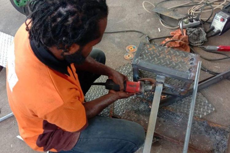 Yason Agapa merakit kompor berbahan bakar oli bekas.
