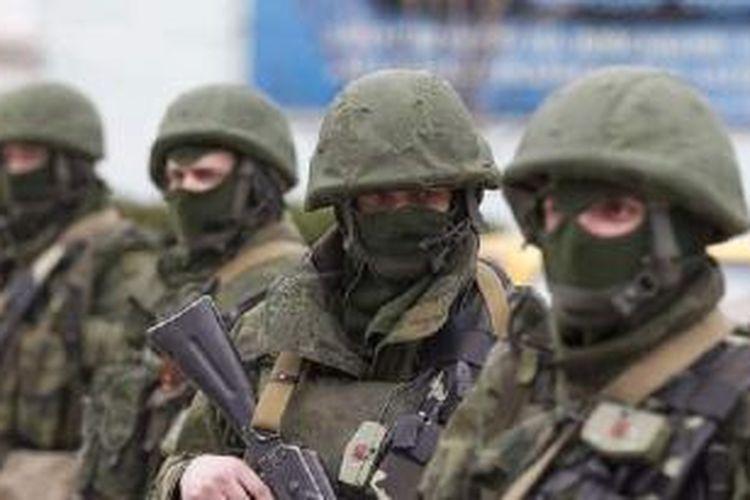 Tentara bersenjata berdiri di luar sebuah pos penjaga perbatasan Ukraina di kota Balaclava, Crimea