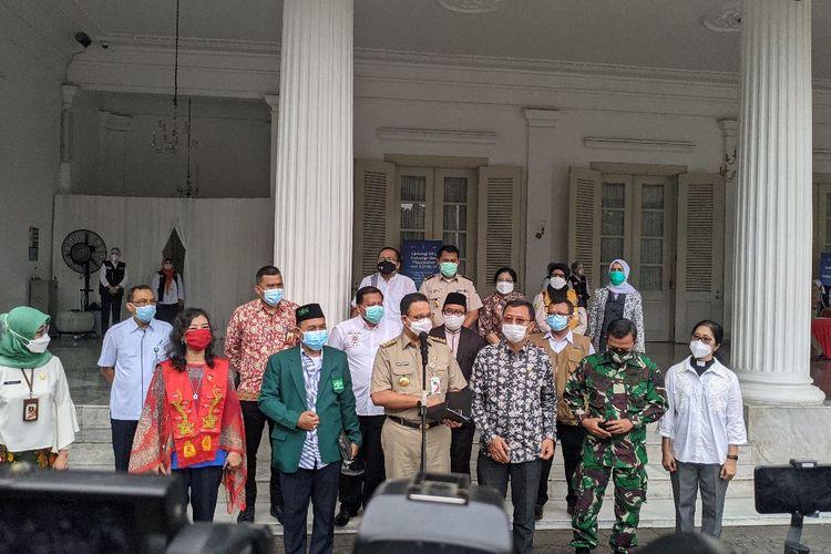 Gubernur DKI Jakarta Anies Baswedan (depan mikrofon) memberikan keterangan pers setelah acara pencanangan Covid-19 di Balai Kota DKI Jakarta, Jumat (15/1/2021)