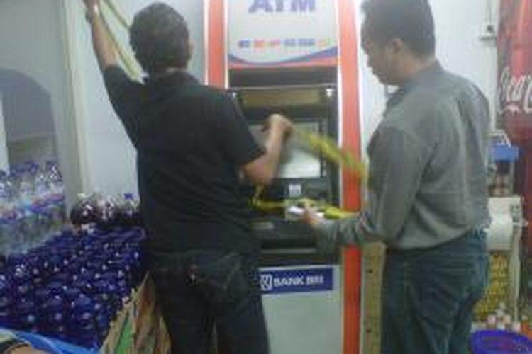Tim penyidik dari Kepolisian Jakarta Utara sedang memeriksa mesin ATM yang dibobol menggunakan las di salah satu mini market di Semper Barat, Cilincing, Jakarta Utara.