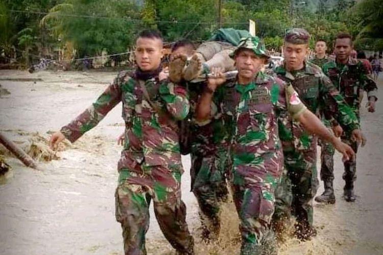 Prajurit TNI tengah mengevakuasi korban banjir bandang