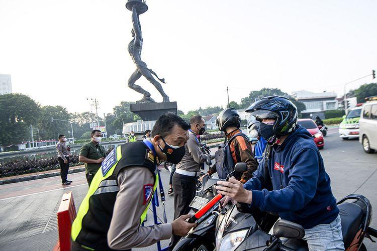 Anggota Polisi memeriksa identitas pengendara sepeda motor saat berlangsungnya Pemberlakuan Pembatasan Kegiatan Masyarakat (PPKM) Darurat di kawasan Bundaran Senayan, Jakarta, Sabtu (3/7/2021). Petugas akan memberikan akses untuk melintas di titik penyekatan PPKM Darurat di 63 titik di wilayah Jadetabek yang berlaku dari 3 - 20 Juli 2021 hanya yang masuk kategori sektor-sektor esensial. ANTARA FOTO/M Risyal Hidayat/hp.