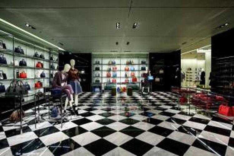 Zona tas wanita dan aksesori ditandai furnitur baja mengkilap dan lantai marmer kotak-kotak monokromatik khas Prada klasik.