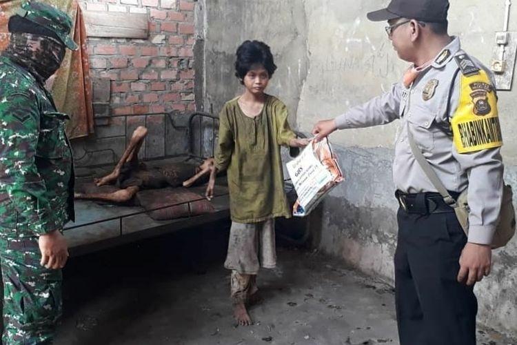 Foto saat personel TNI-Polri memberikan bantuan pada kedua kakak beradik Daluna dan Rohima di Kecamatan Gelumbang  Muara Enim yang videonya viral karena dikatakan kelaparan karena dua hari tidak makan.
