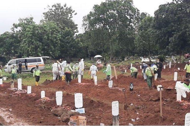 Suasana pemakaman jenazah dengan protap Covid-19 di TPU Bambu Apus, Cipayung, Jakarta Timur, Minggu (24/1/2021).