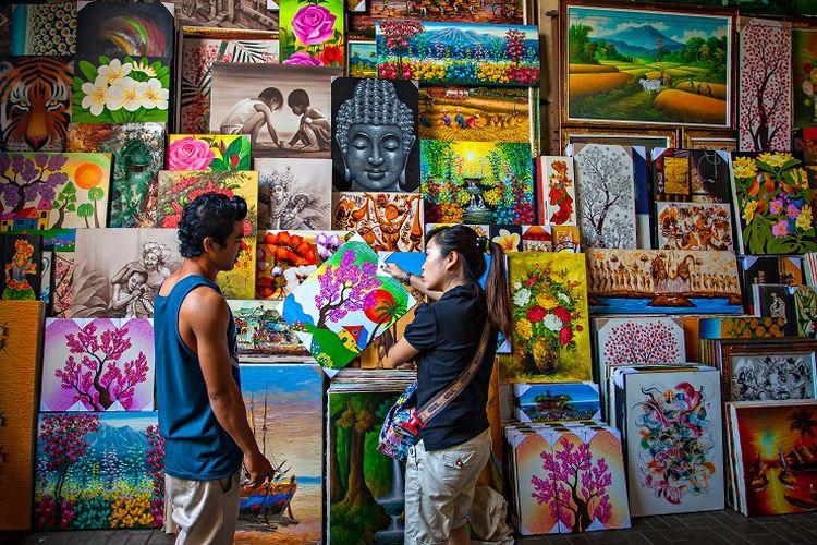 Seorang penjual lukisan dan pembeli di Pasar Seni Sukawati, Bali.