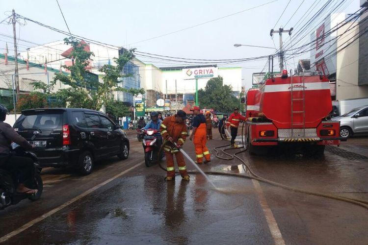 Petugas Dinas Pencegahan dan Penanggulangan Kebakaran Kota Bandung saat membersihkan lumpur di Jalan Purwakarta pasca banjir bandang, Rabu (21/3/2018).