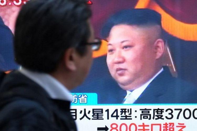 Seorang pejalan kaki melewati televisi yang menayangkan gambar pemimpin Korea Utara, Kim Jong Un, di jalanan Tokyo, Jepang. Kim Jong Un menyebut kesuksesan Korea Utara meluncurkan Hwasong-15 telah membuat mereka sebagai negara nuklir sejajar dengan Amerika Serikat maupun Rusia. (29/11/2017)
