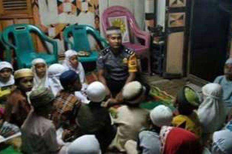 Bripda Muh Rivadi Pradana, anggota Polres Bima saat mengajiri anak-anak menjadi di desa binaanya.