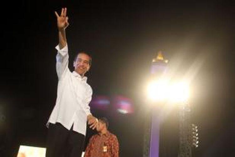 Presiden Joko Widodo atau dipanggil Jokowi saat berlari diatas panggung pada acara syukuran rakyat salam 3 jari di Komplek Monas, Jakarta Pusat, Senin (20/10/2014).