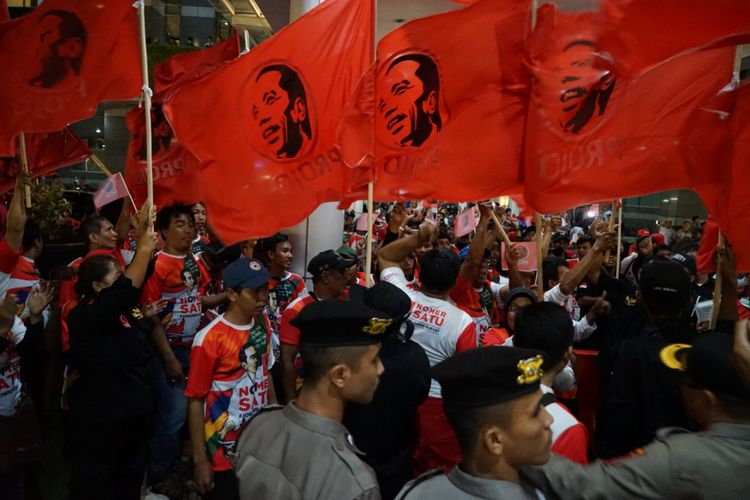Kelompok relawan Projo turut memberikan dukungan kepada pasangan capres-cawapres nomor urut 01 Joko Widodo-Maruf Amin saat debat pertama Pilpres di Hotel Bidakara, Jakarta Selatan, Kamis (17/1/2019) malam.  Mereka memadati bahu jalan yang menuju lobbby Hotel Bidakara. Ratusan pendukung itu membawa bendera berwarna merah dan bergambar wajah Jokowi.