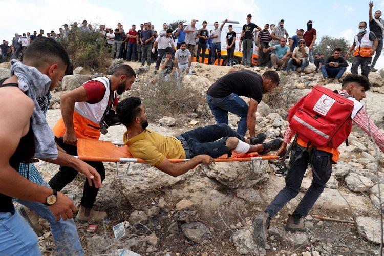 Petugas medis mengevakuasi seorang warga Palestina yang terluka dalam bentrokan dengan tentara Israel di Beita, dekat kota Nablus, Tepi Barat, pada Jumat (23/7/2021). Warga Palestina memprotes pembangunan pos terdepan di Eviatar yang melanggar hukum internasional dan Israel sendiri.