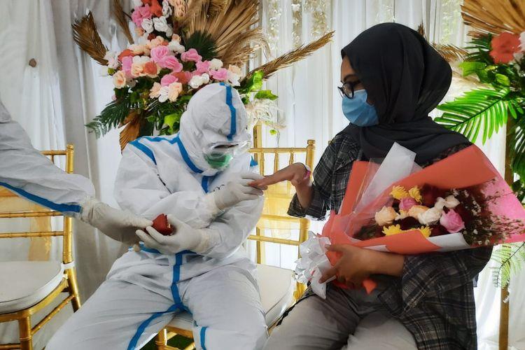 Mengenakan APD lengkap, Pringgo Aditya menyematkan cincin pernikahan kepada sang istri Aini Ummia yang sedang diisolasi di RSD Wisma Atlet Kemayoran, Jakarta Pusat, usai menggelar pernikaham virtual pada Jumat (1/1/2021).
