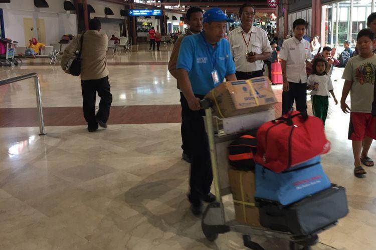 Petugas airport helper sedang membawa barang penumpang dengan troli di Terminal 2 Bandara Soekarno-Hatta, Tangerang, Selasa (10/10/2017).