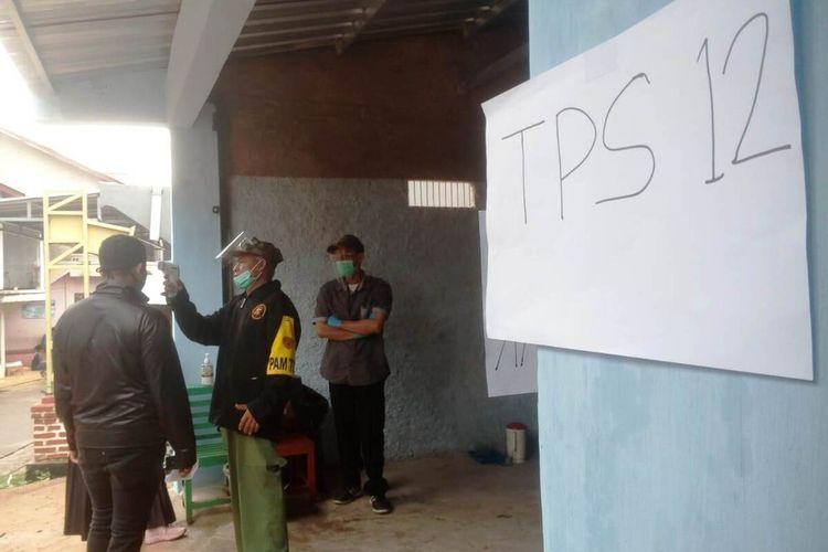 Seorang petugas KPPS di Desa Bunisari, Kecamatan Warungkondang, Kabupaten Cianjur, Jawa Barat, tengah mengecek suhu tubuh warga yang hendak menyalurkan hak pilihnya dalam pemungutan suara ulang Pilkada Cianjur 2020, Minggu (13/12/2020).