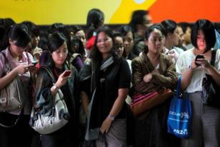 Pengguna Kereta Rel Listrik mengoperasikan telepon genggam mereka saat menunggu datangnya kereta di peron Stasiun Sudirman, Dukuh Atas, Jakarta Pusat, beberapa waktu lalu.