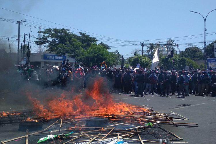 Ribuan Mahasiswa dsri berbagai kampus di Makassar saat membakar karangan bunga berisi ucapan selamat anggota DPRD Sulsel yang baru, Selasa (24/9/2019).