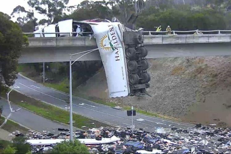 Truk pengangkut produk unggas mengalami kecelakaan di Melbourne, Victoria, sehingga menyebabkan sebagian badan truk bergelantungan di jalan layang, pada Selasa (20/11/2018). (VicRoads via BBC)
