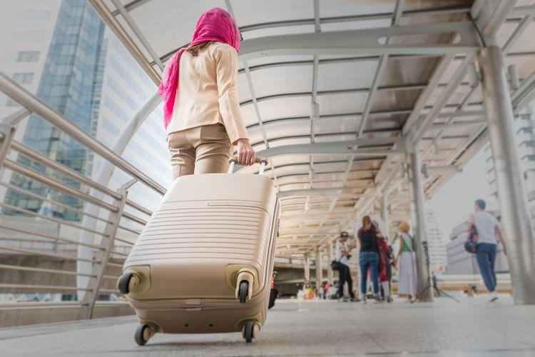 Ilustrasi perempuan bawa koper.